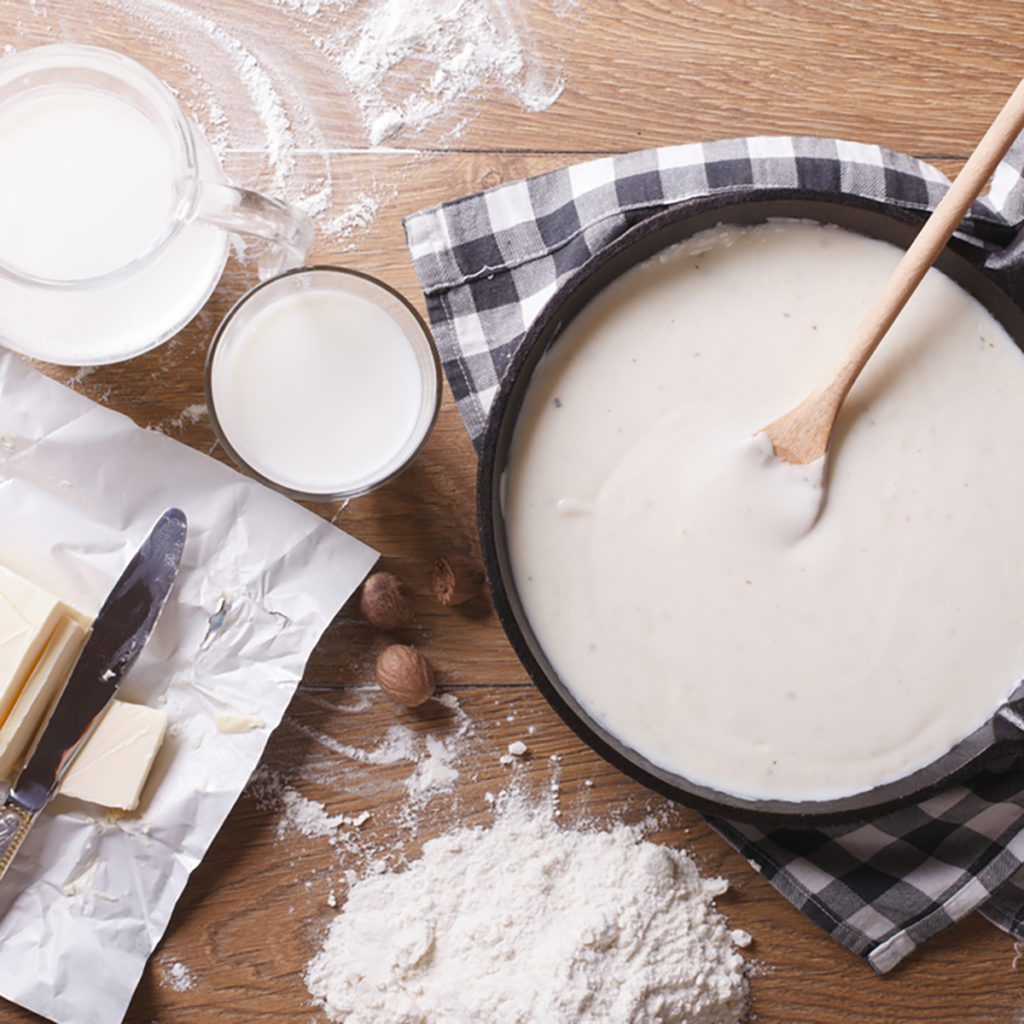 Preparation of bechamel sauce in a pan and ingredients on the table. horizontal view from above