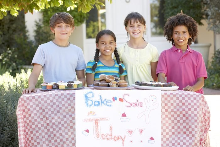 Group Of Children Holding Bake Sale