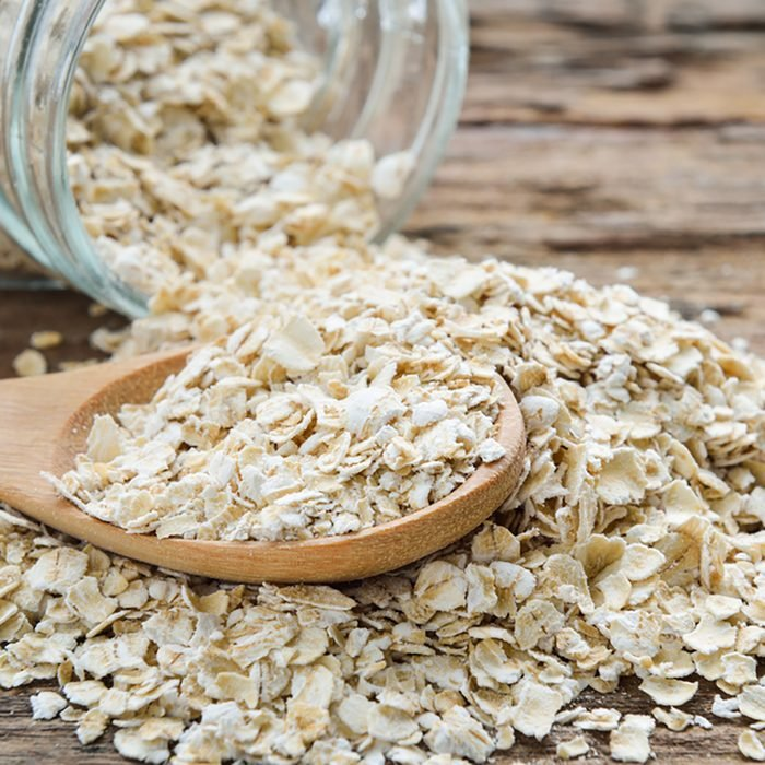 Dry rolled oat flakes oatmeal on old wooden table