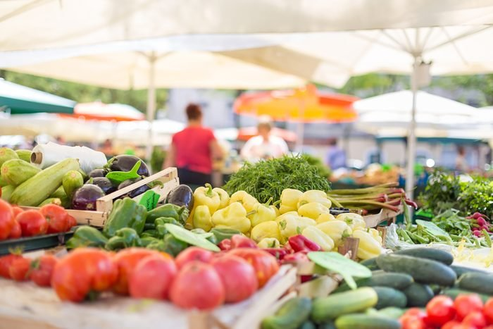 Farmers' food market stall with variety of organic vegetable. Vendor serving and chating with customers.