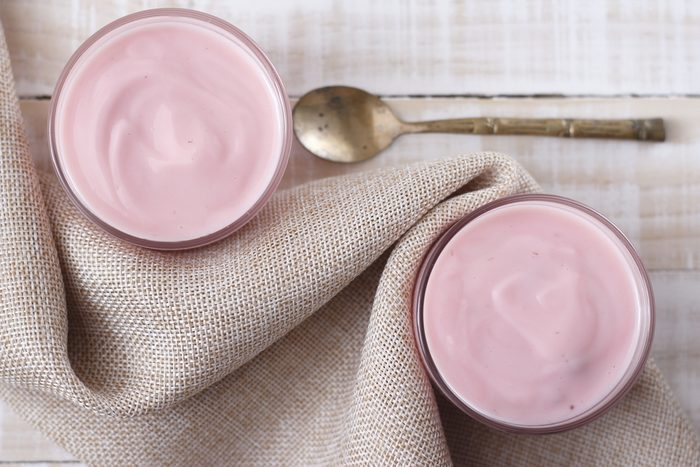strawberry yogurt in glass with vintage spoon and cloth place on white wooden background. pink yogurt. pink yoghurt, strawberry yoghurt.