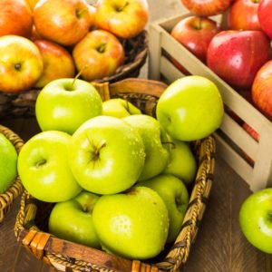 Variety of organic apples in baskets on wood table