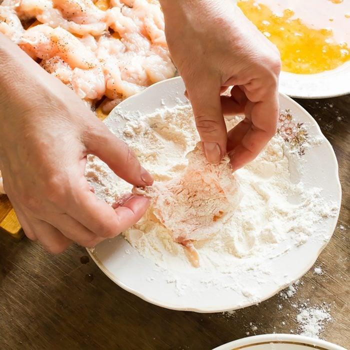 Raw chicken fillet in flour;