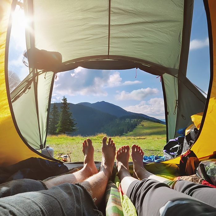 Two people lying in tent with a view of mountains.