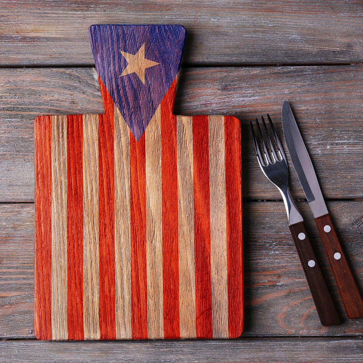 Cutting board with fork and knife on rustic wooden planks background. American cuisine food concept