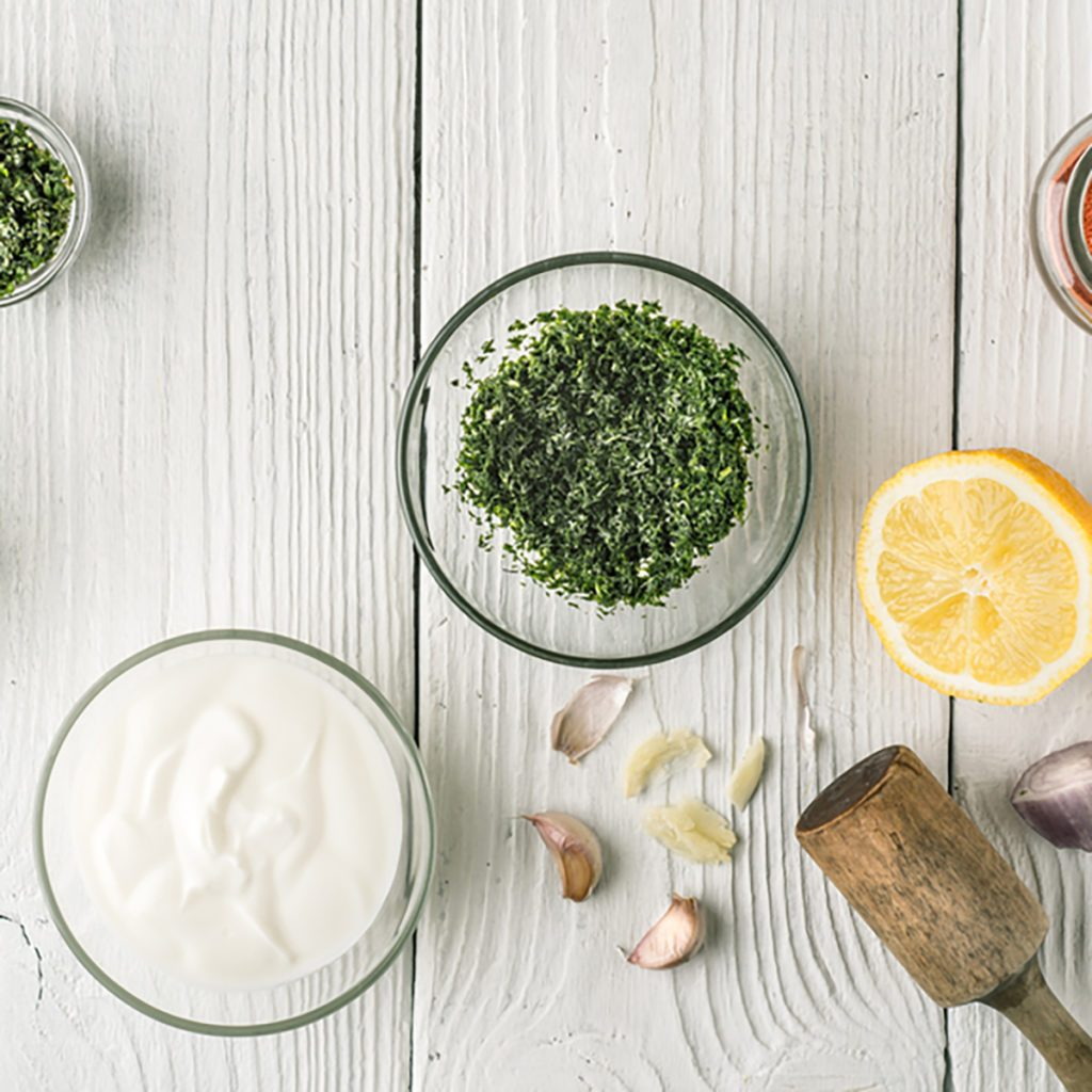 Natural yogurt and different seasoning on the white wooden table top view; Shutterstock ID 430402339