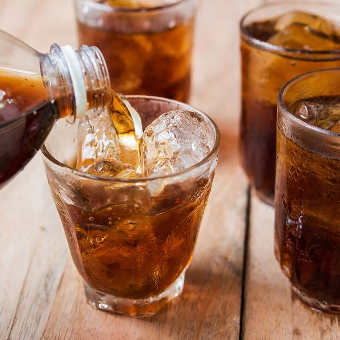 Cola drink is poured into a glass with ice
