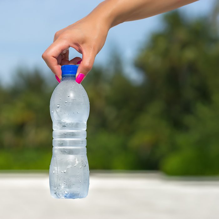 Woman hand holding water bottle outdoors