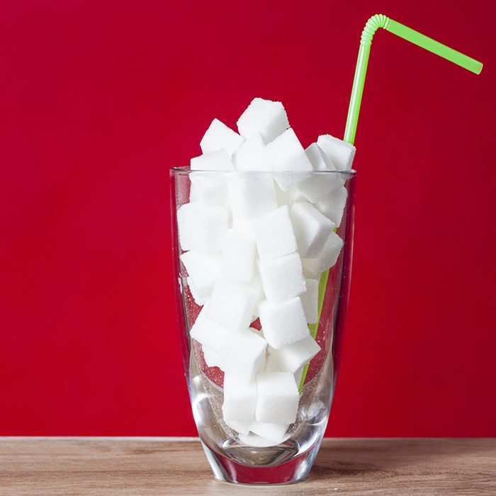 Glass with straw full of sugar and sugar cubes on red background