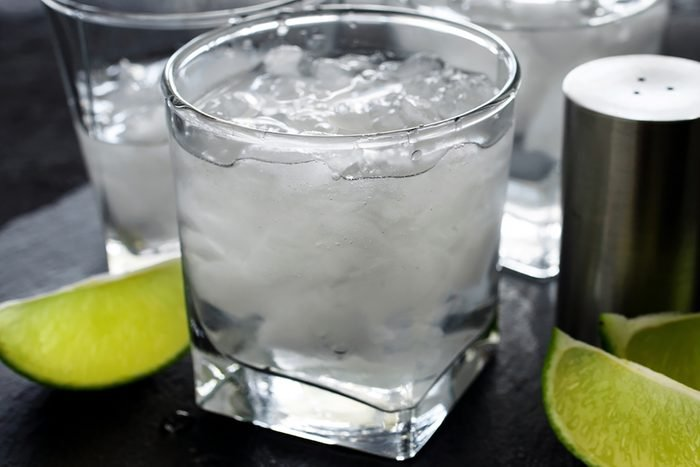 Gin and tonic with ice and lime on a dark background close up