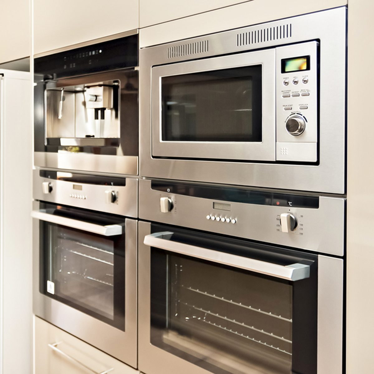 Luxurious kitchenware including silver oven and refrigerator in the kitchen which has a wooden floor, Pantry cupboards are light brown color and installed around the cooker and fridge. ; Shutterstock ID 469237499