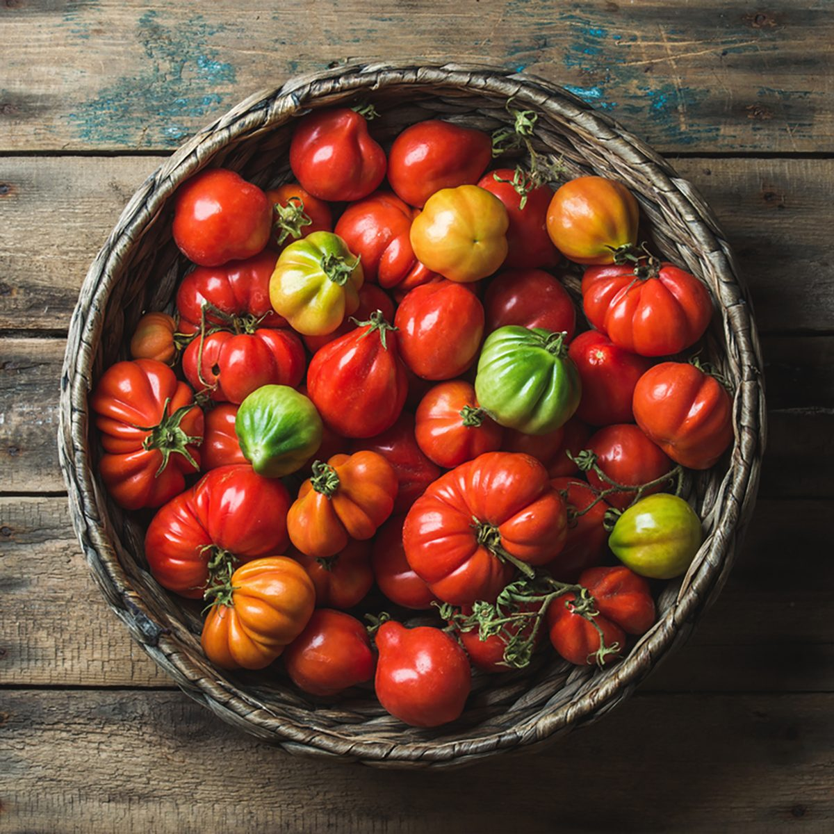 Fresh colorful ripe heirloom tomatoes in basket over wooden background
