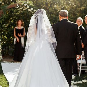 Look from behind at father leading bride in luxuriant wedding dress to altar