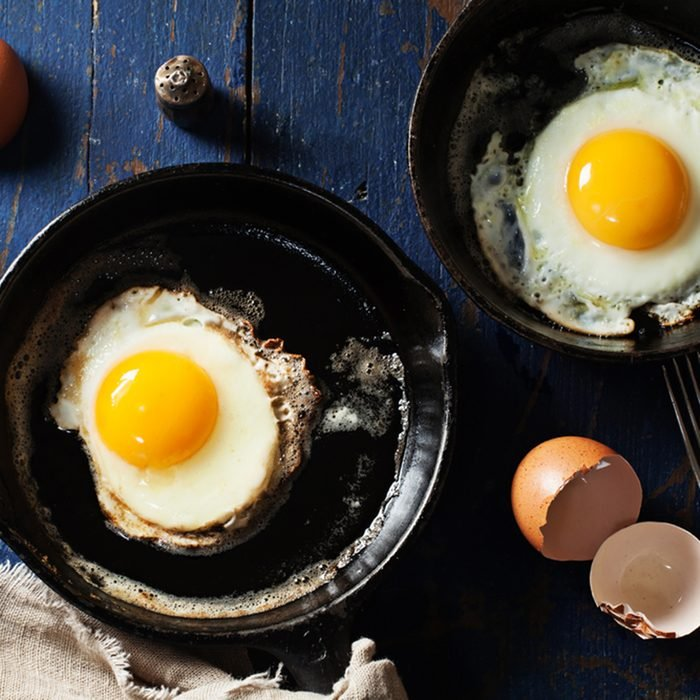 Old-fashioned fried eggs in cast-iron skillets on wooden background