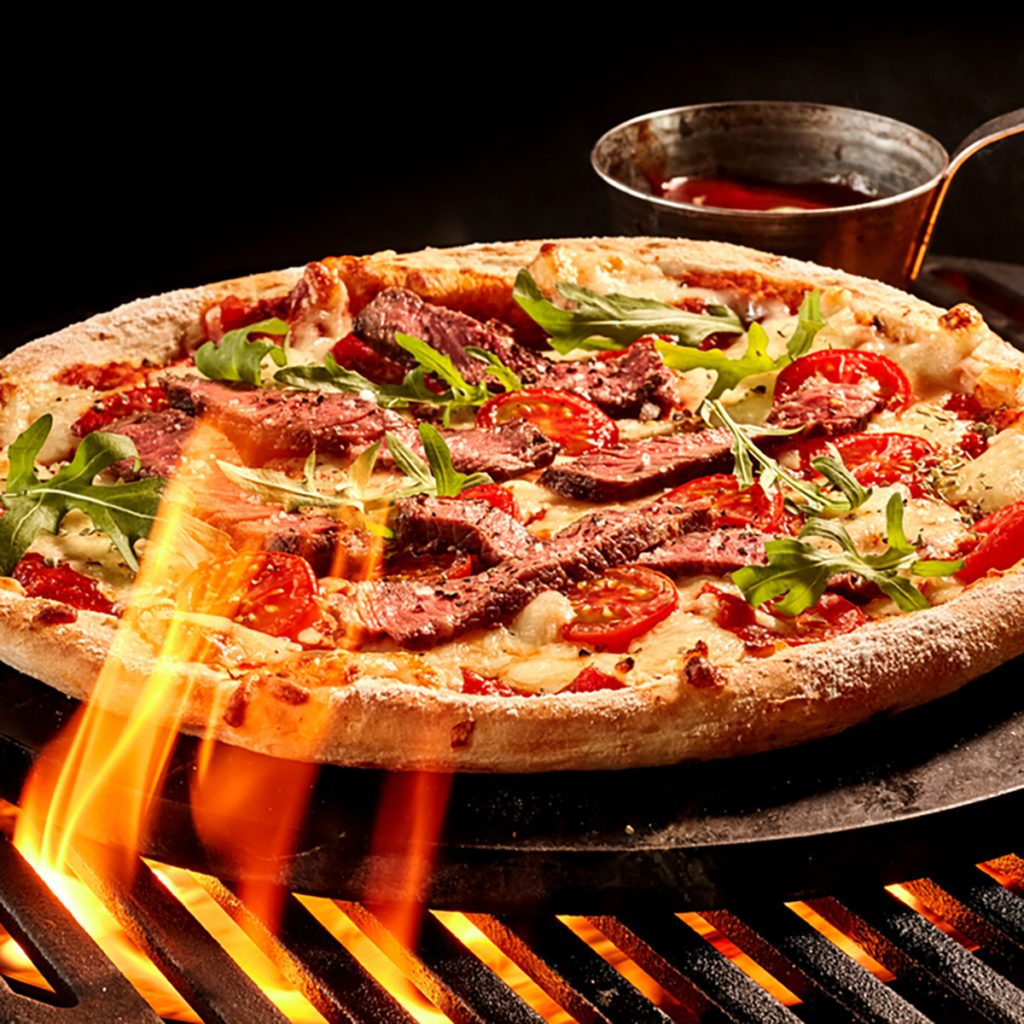 Flames reaching up toward meat and vegetable cheese pizza on grill. Hot sauce in bowl on iron plate