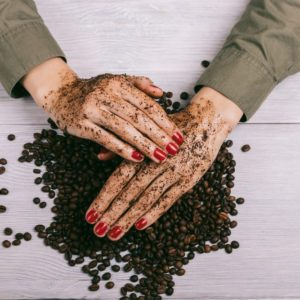 Women's hands with red nail polish applied the coffee scrub