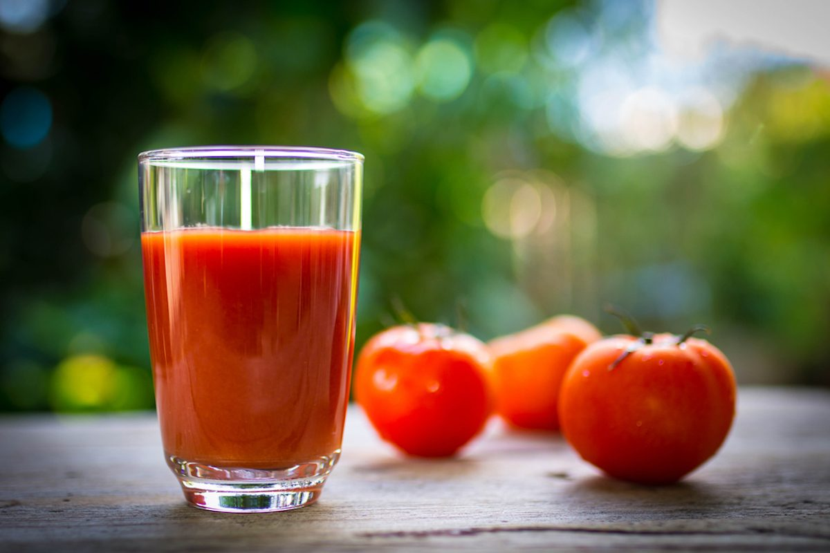 Tomato juice in clear glass on wooden table