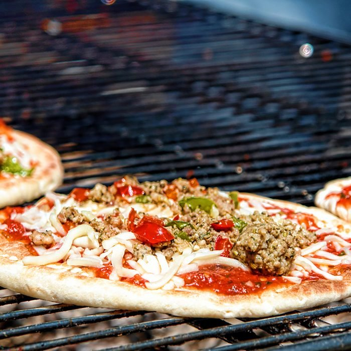 Pizza pie with sausage and peppers cooking on a charcoal grill in an Italian pizzeria