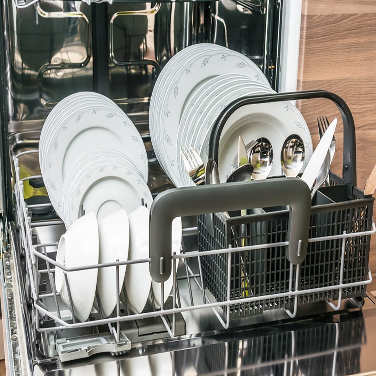 Open dishwasher with clean dishes after cleaning process.