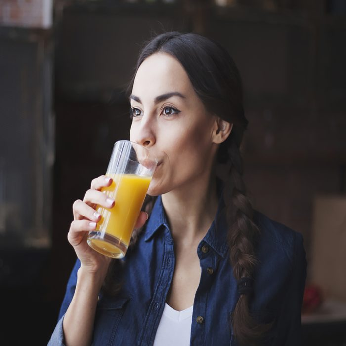 Portrait of very beautiful young brunette girl in jeans shirt on a kitchen at home. The girl drinks orange juice from transparent glass.
