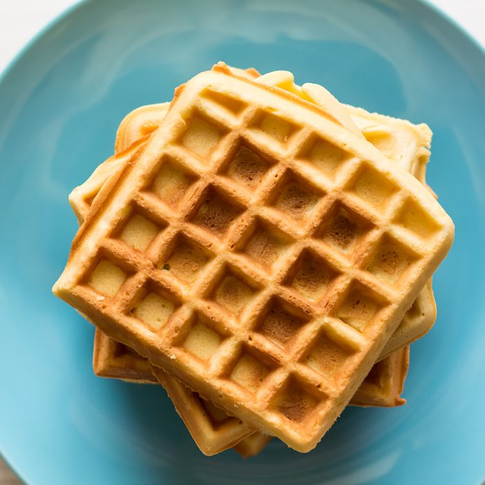 Belgian waffles with honey and cranberries on blue plate. Selective focus