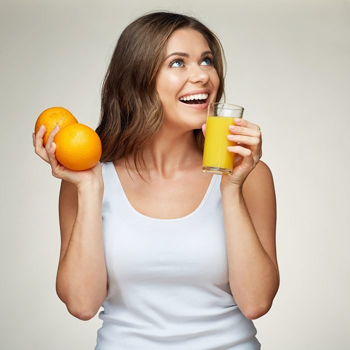 sporty woman drink orange juice and holds fruit.