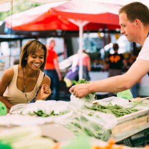 Smiling black woman buying fresh vegetables at farmer's market