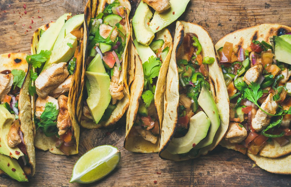 Tacos with grilled chicken, avocado, fresh salsa sauce and limes over rustic wooden background