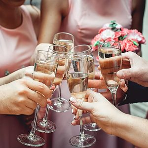 People hold in hands glasses with white wine. wedding party. friends toasting with a champagne