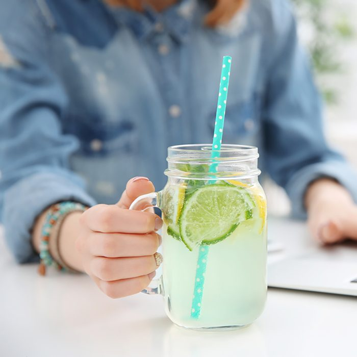 Young woman with lemonade and laptop in cafe, closeup;