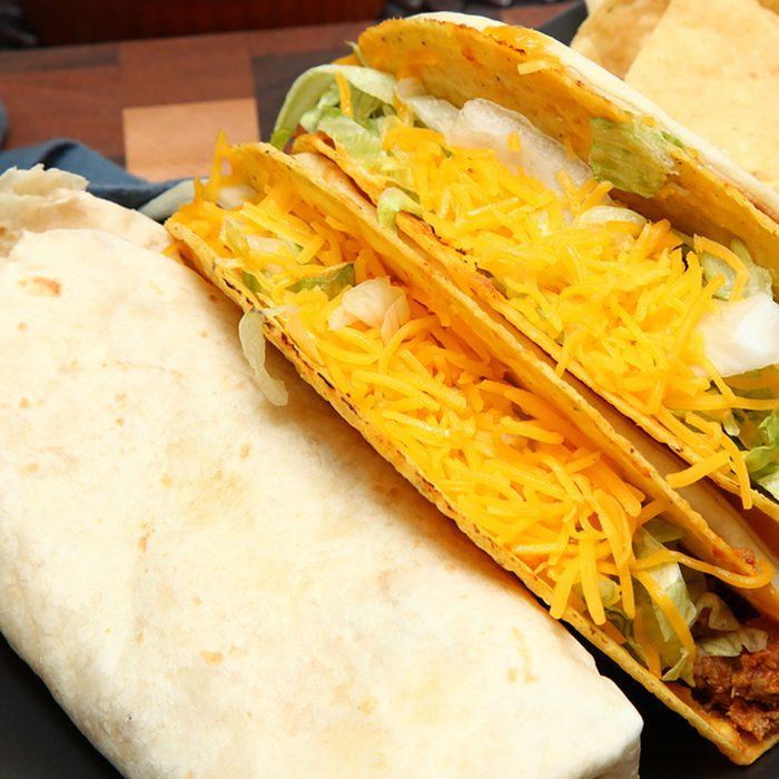 Burrito, Taco, Gordita Crunch and Nachos with Cheese Sauce on Dish.