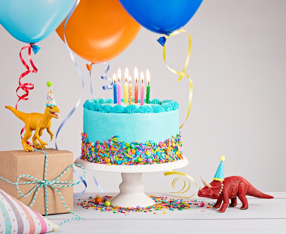 Childs Birthday Party Scene With Blue Cake Gift Box Toy Dinosaurs Hats And