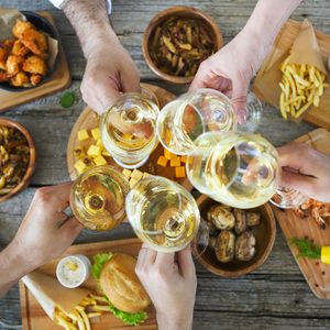 Hands with white wine toasting over served table with food. Friendship and happiness concept.