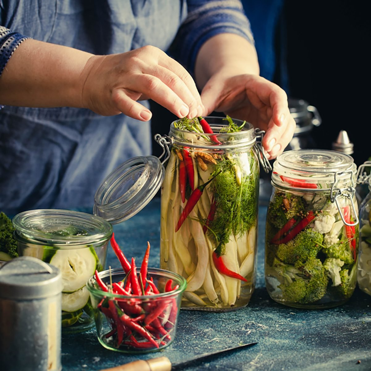Canning green beans with red hot chili peppers in glass jars with pickled cabbage cauliflower broccoli sour preserved hands add herbs fermented process.