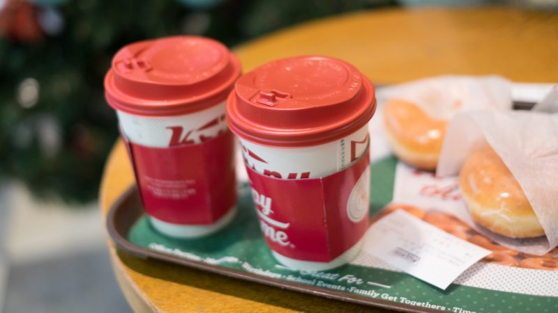 take away hot chocolate beverage served in a tall red Christmas designed cup with sweet krispy kreme donut