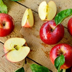 Red apples or Gala apples with fresh leaf and water drop on wooden background.
