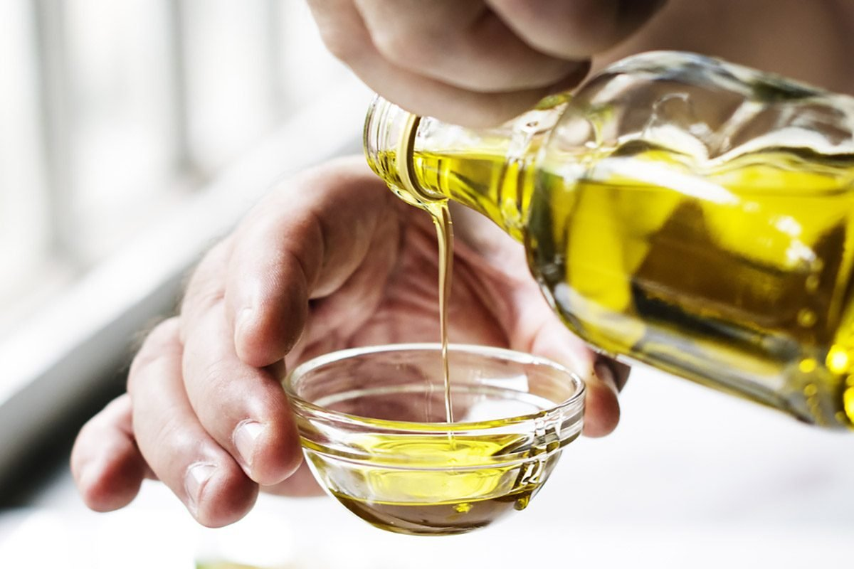 Closeup of hands pouring virgin olive oil