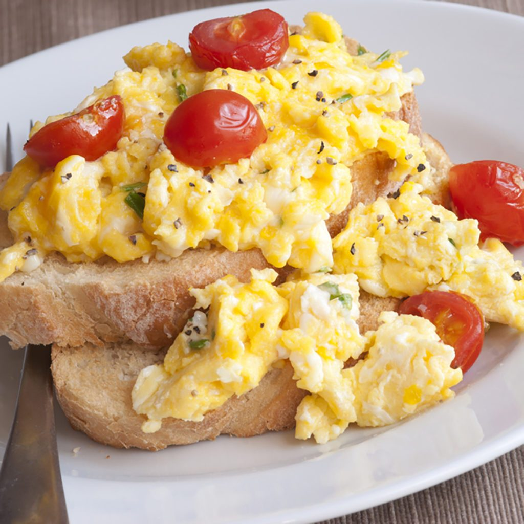 Toast with scrambled eggs and cherry tomatoes