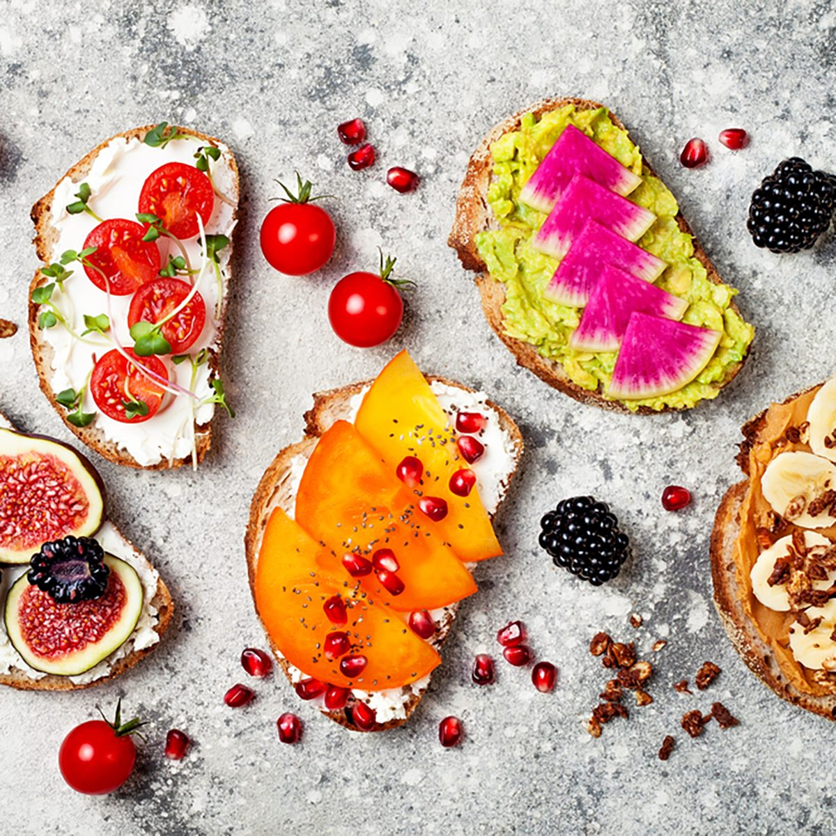 Healthy breakfast toasts with peanut butter, banana, chocolate granola, avocado, watermelon radish, persimmon, pomegranate, chia seeds, tomato, figs, blackberry