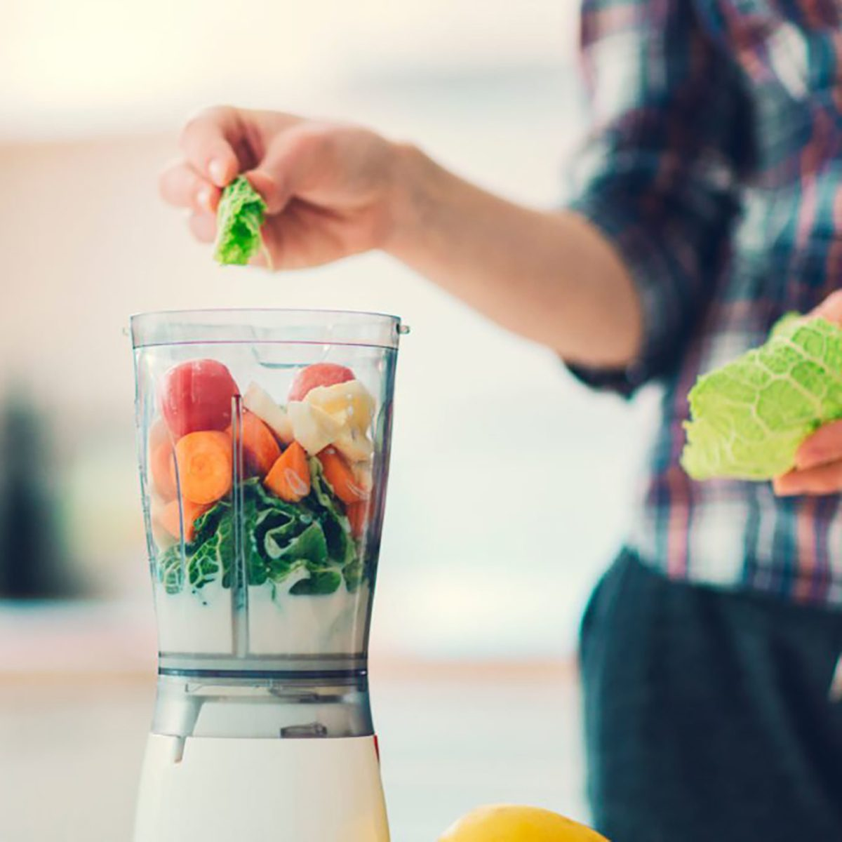 woman adding produce to blender