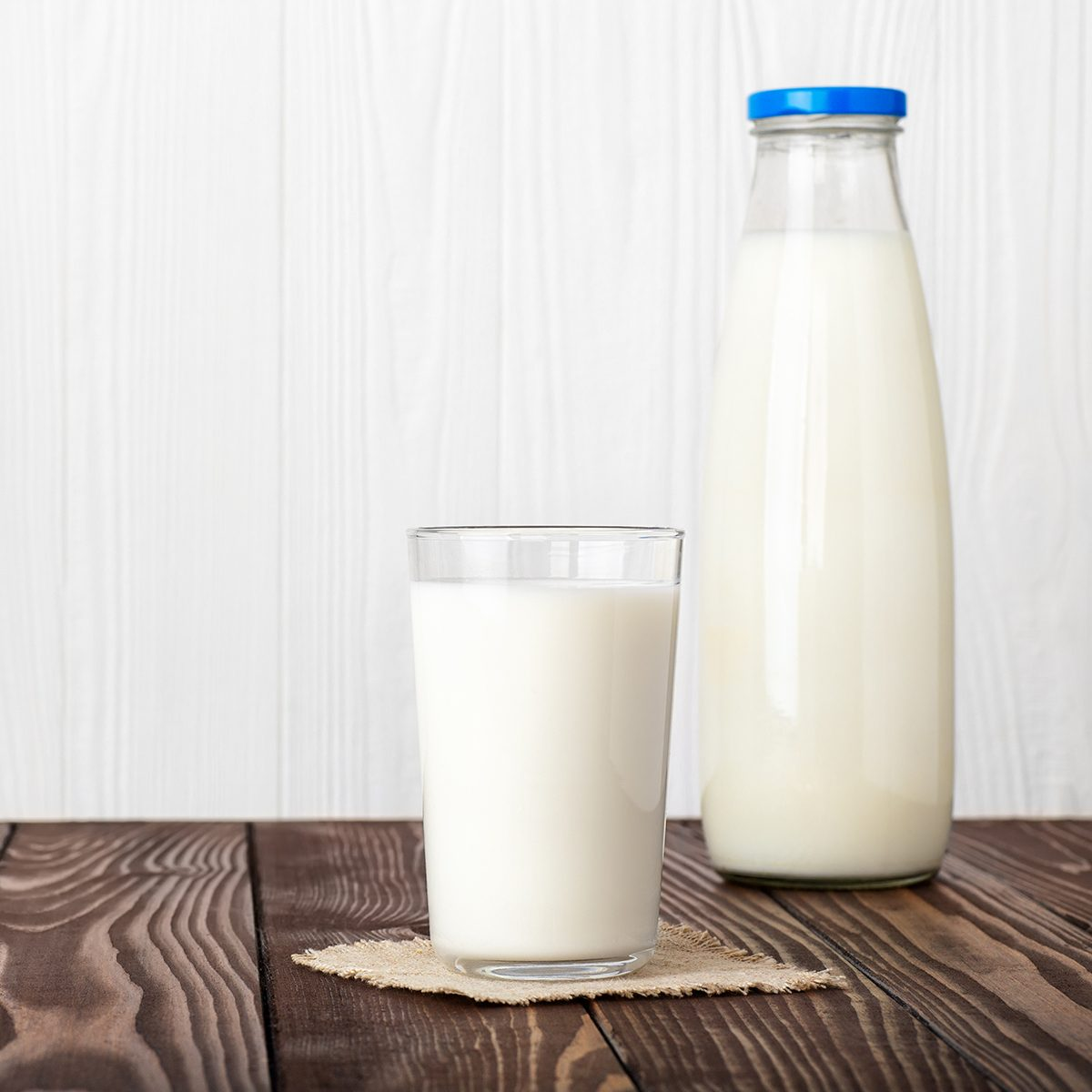 milk in glass and bottle with napkin on wooden table isolated on white background
