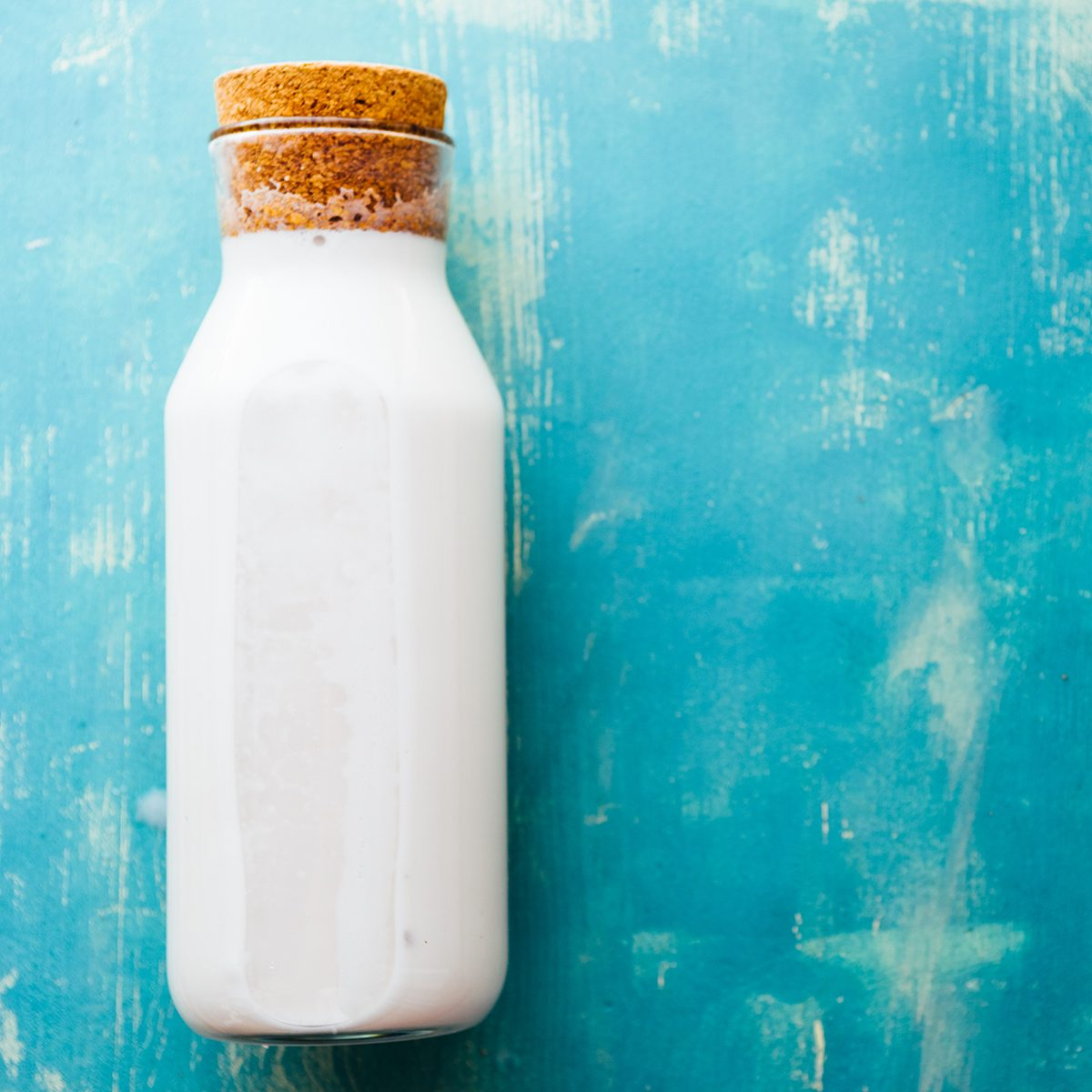 Top view of an Homemade coconut milk in a bottle, made after mixing coconut and water in a blender and pressed through a cotton sieve, over a rusty blue background