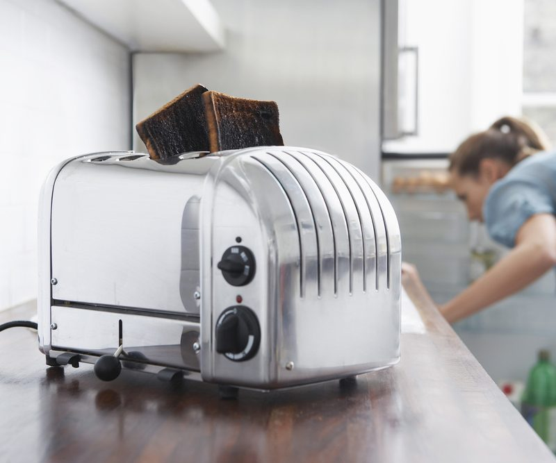 Burned toasts in toaster on kitchen counter with woman in background; Shutterstock ID 144902326; Job (TFH, TOH, RD, BNB, CWM, CM): TOH Amazon Echo