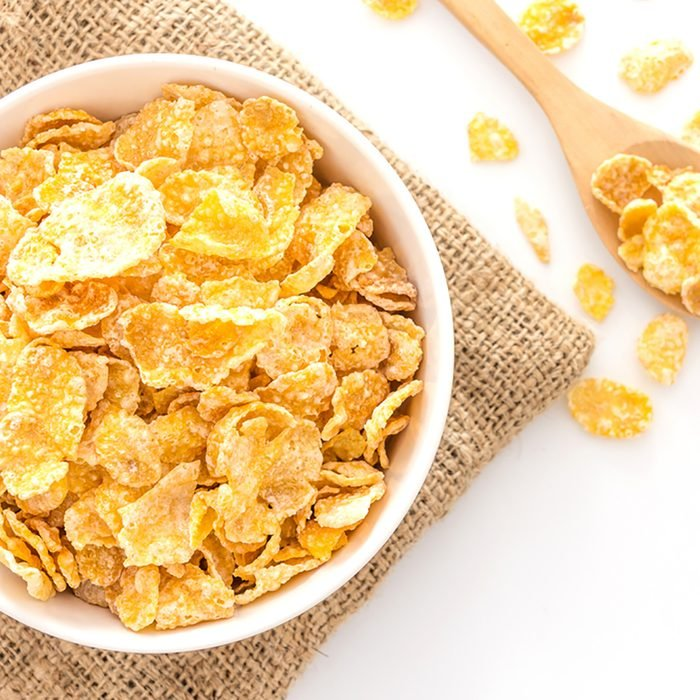 bowl of cornflakes and cornflakes on wooden spoon over a sackcloth on white table background, Top view with copy space; Shutterstock ID 492732964; Job (TFH, TOH, RD, BNB, CWM, CM): Taste of Home