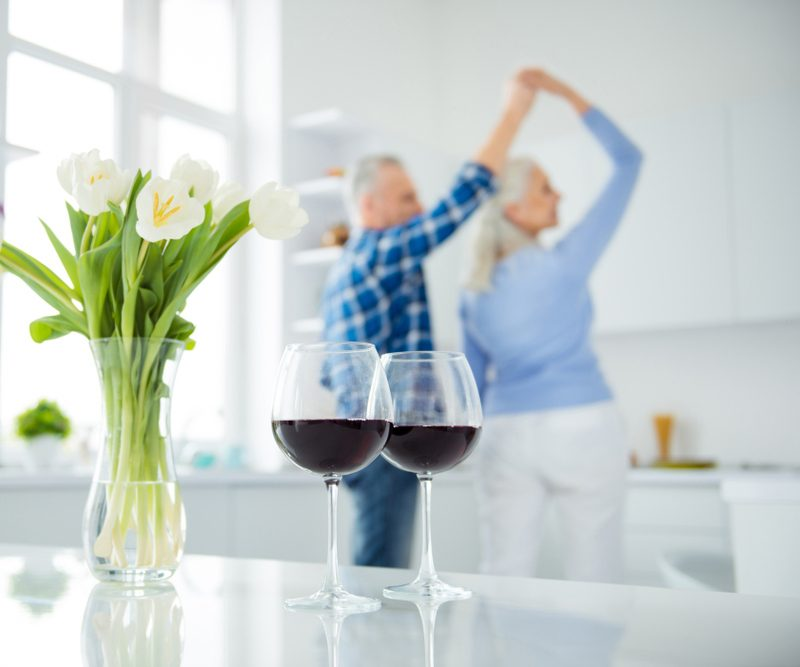 Portrait of lovely happy modern stylish attractive couple, dancing in the kitchen on blurred background, two glasses of red wine, bouquet of tulips in vase standing on the table, spring time; Shutterstock ID 1066518323; Job (TFH, TOH, RD, BNB, CWM, CM): TOH Amazon Echo