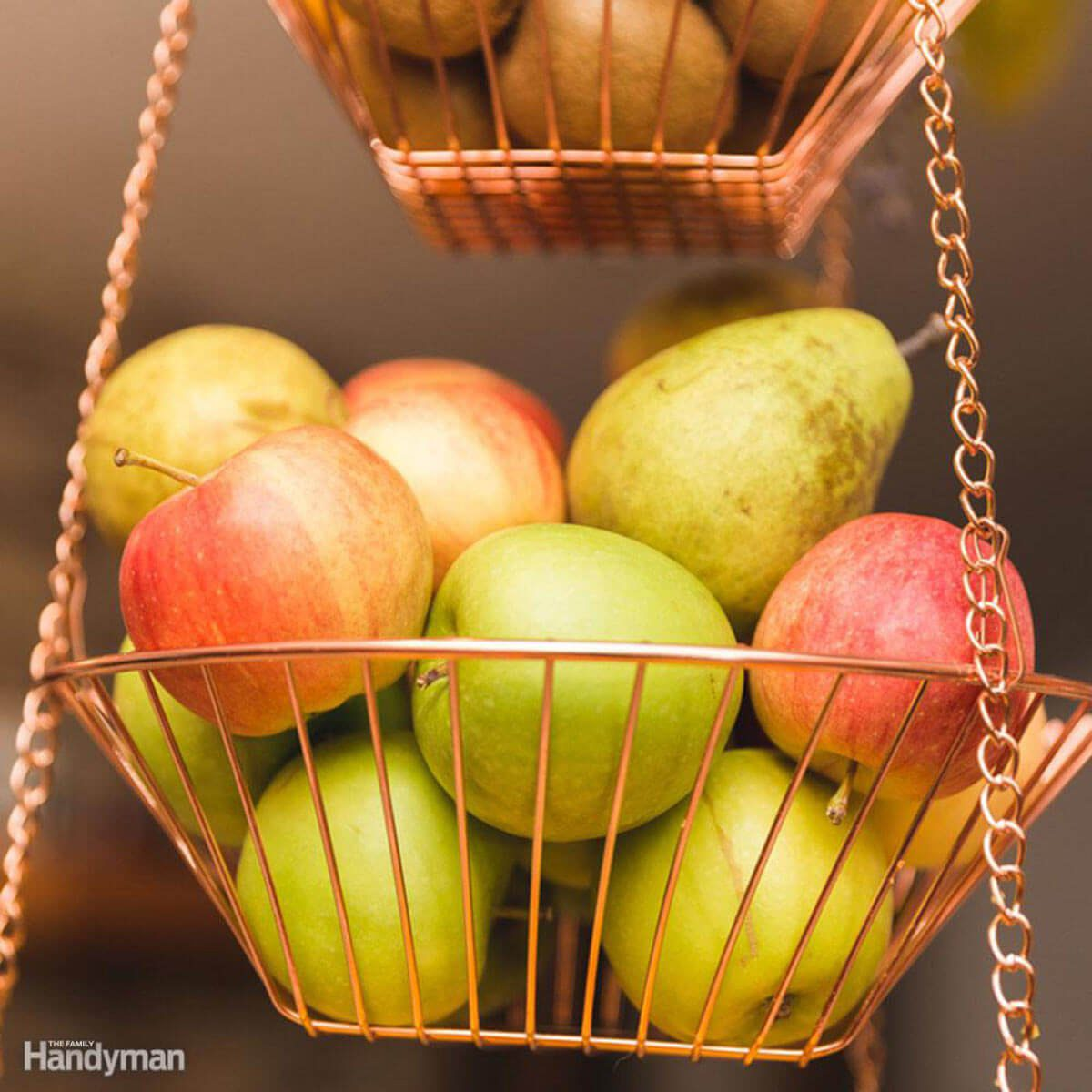 Red and green apples with pears in a hanging metal basket inside a kitchen.