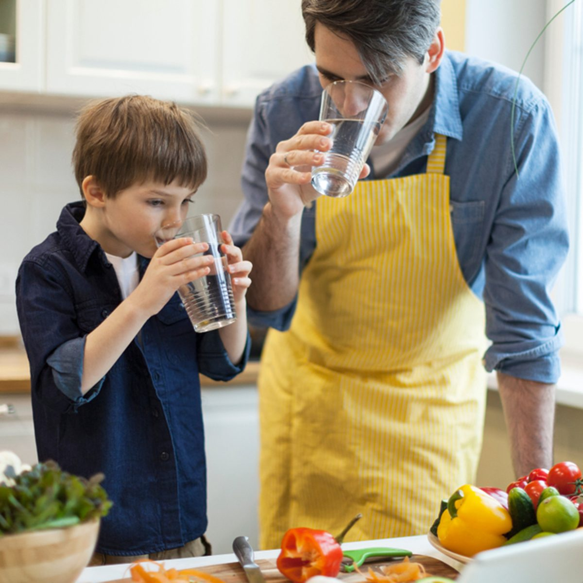 Father and son cooking healthy food in the kitchen and drinking water