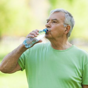Senior man is drinking water after workout in park.