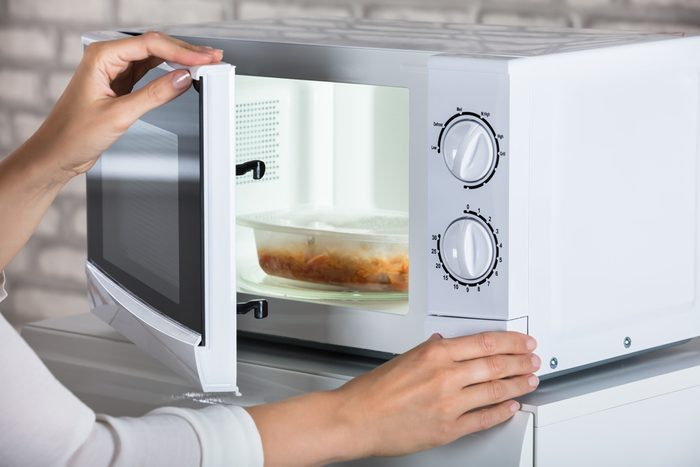 Woman's Hands Closing Microwave Oven Door And Preparing Food At Home; Shutterstock ID 694624951; Job (TFH, TOH, RD, BNB, CWM, CM): TOH How To Microwave