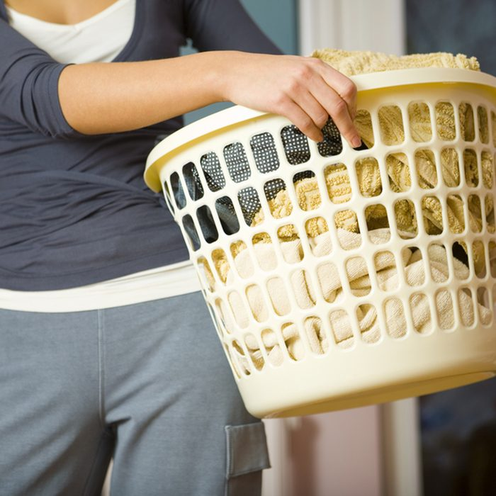 Woman standing and holding in hands full laundry basket.